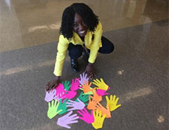 Woman leans over colored cut outs of hands