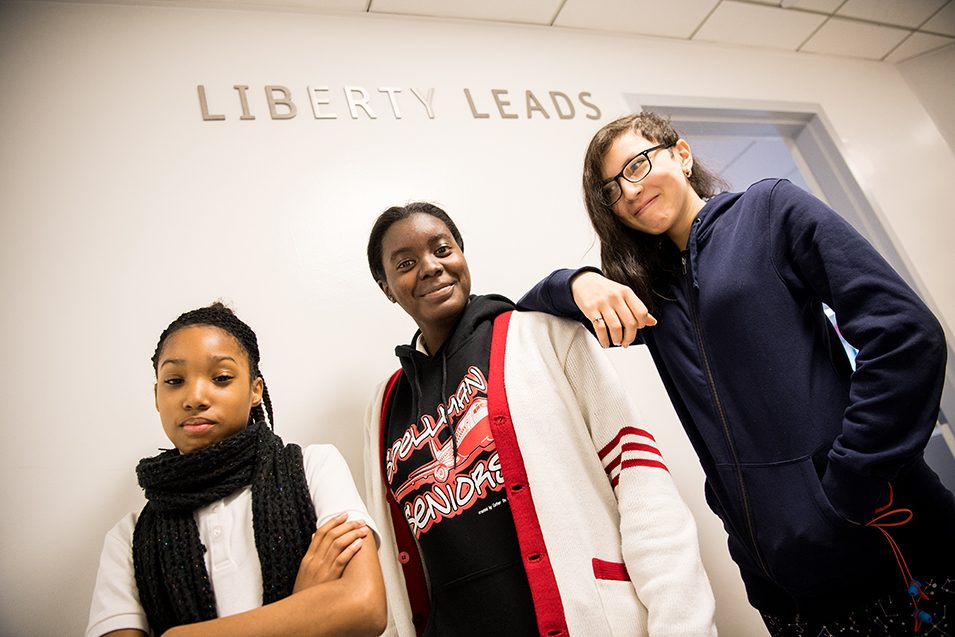 Three Liberty Leads students standing outside of the Liberty Suite.