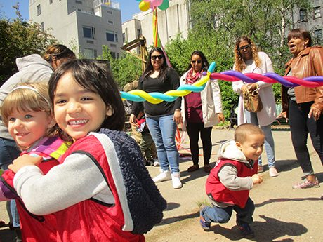 A group of parents and children are smiling at the May day celebration.
