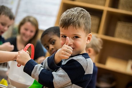 Child in the Family Center giving a thumbs up signal