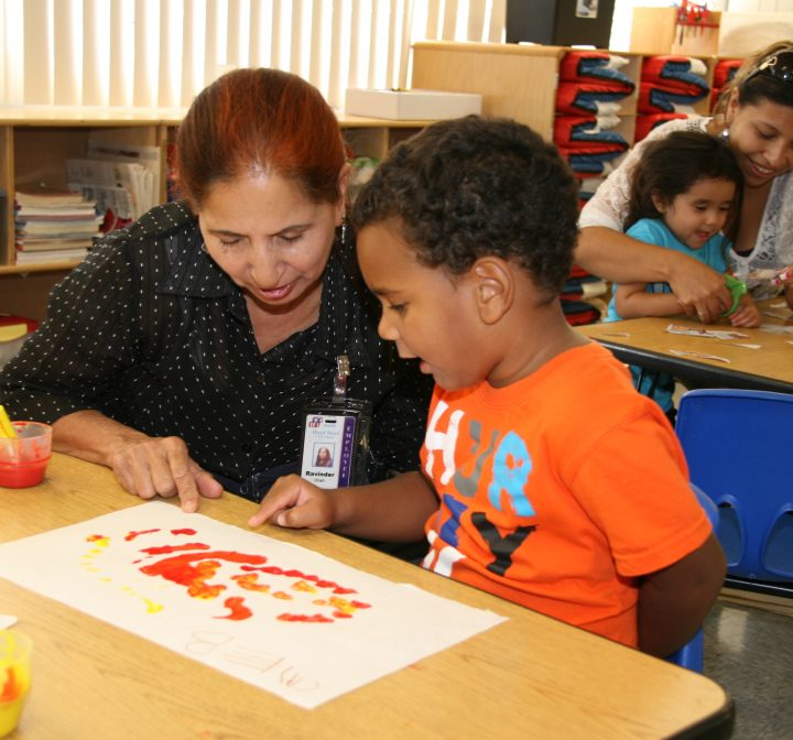 Young African American boy paints with teacher