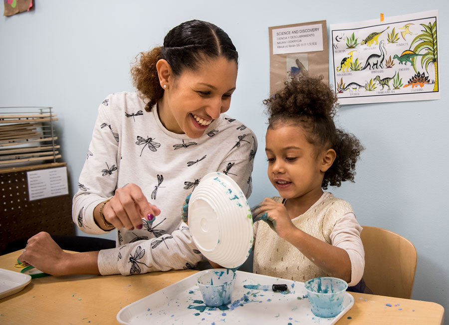 Teacher helps student paint