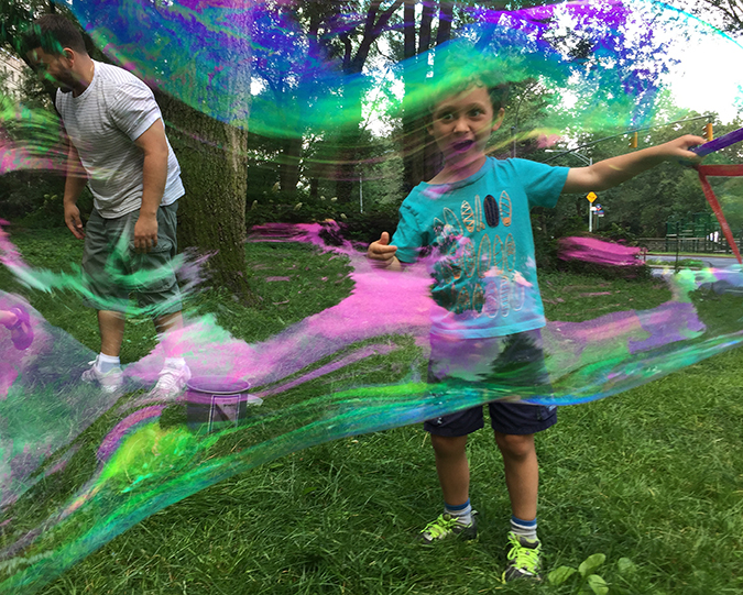 Preschooler making a huge colored bubble