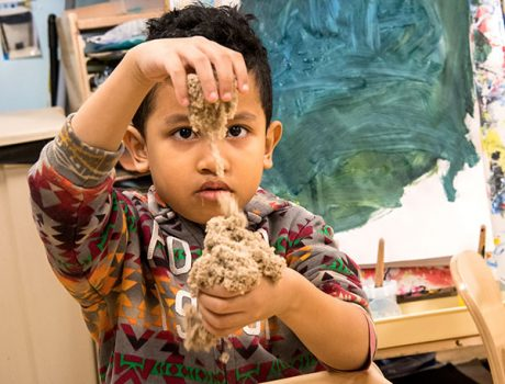 Boy working with sand to learn by doing