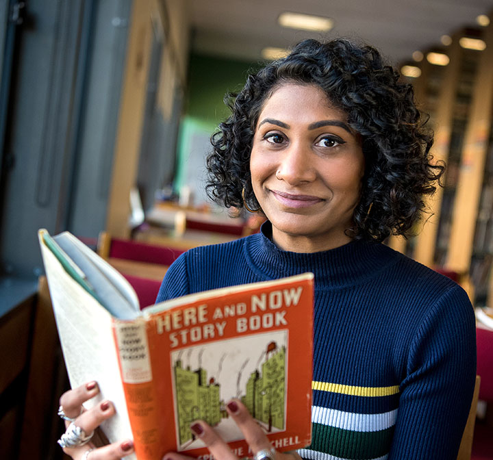 Grad student holds Here and Now Story Book