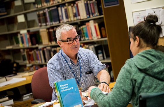 Peter Hare helps a student in the Library