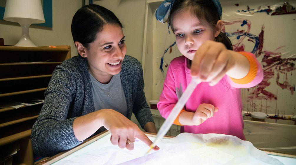 Child at a light table with a teacher