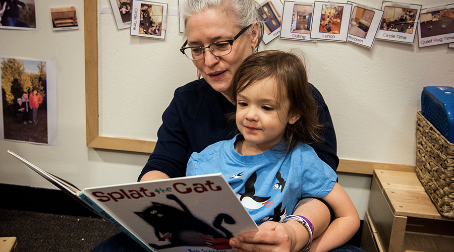 Teacher reading to child at the Family Center