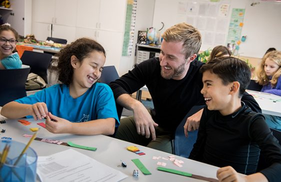 Teacher and two students smiling while working