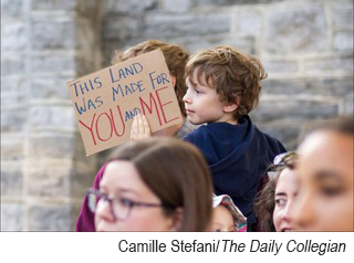 Child holding patriotic sign on street