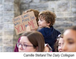Child holding patriotic sign during protest