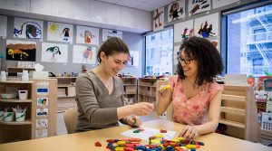 Two graduate students using math manipulatives