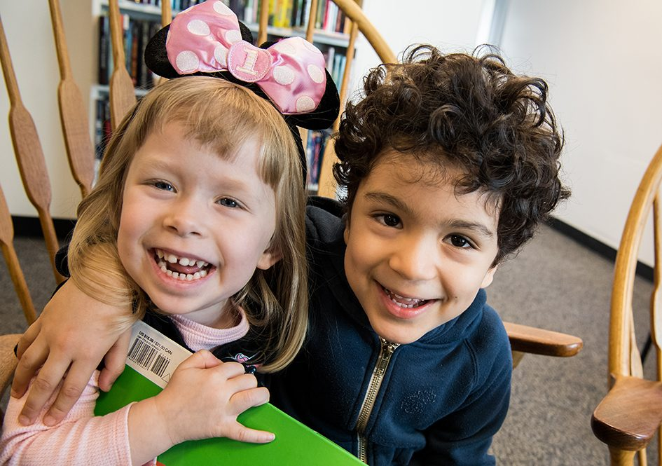 Two kids smiling in library