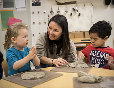 Teacher and two young children play with clay