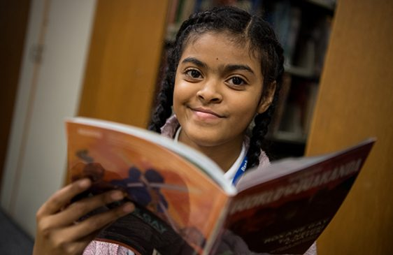 Liberty LEADS student smiling while holding book