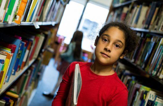 Child in library bookshelves