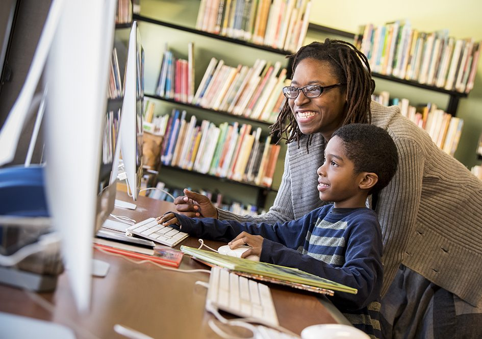 Teacher and child look at library computer