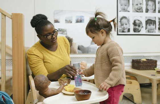 Teacher and young child feed baby doll