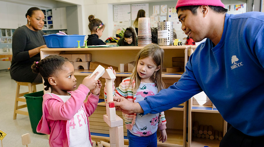 Teacher and two children building with blocks