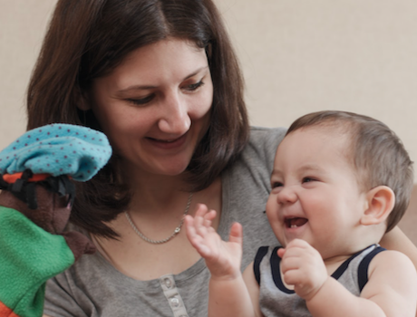 Caregiver holds baby and puppet
