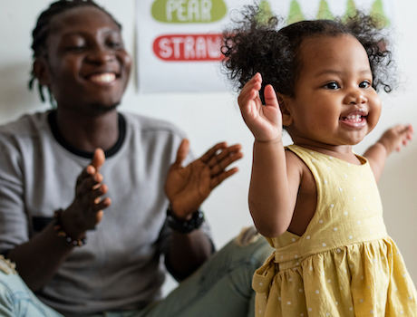 Caregiver and young child smiling