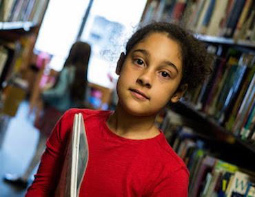 Child in between bookshelves