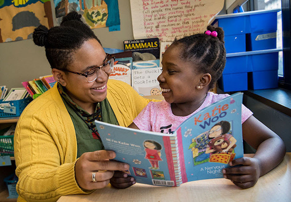 Child and teacher read a book together