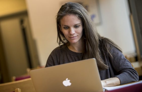 Graduate student typing on laptop in library