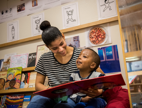 Teacher and young child reading together