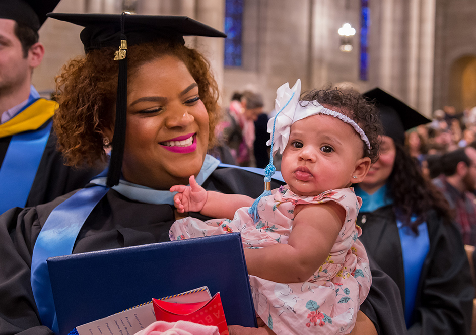 Graduate holding baby