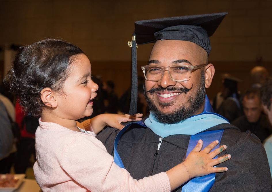 Graduate holding child