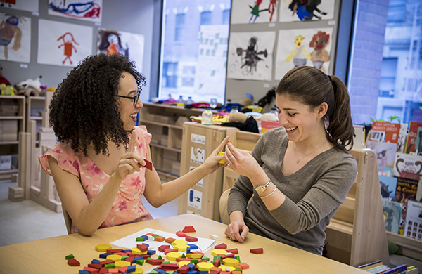 Two graduate students playing with math manipulatives