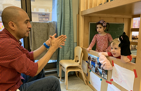 Teacher watching two children do a puppet show