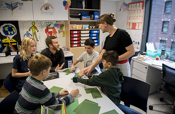 Faculty advisor and graduate student working with children in a classroom