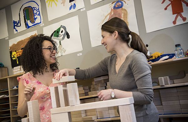 Two graduate students building with blocks