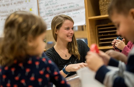 Blonde grad student smiling with kids