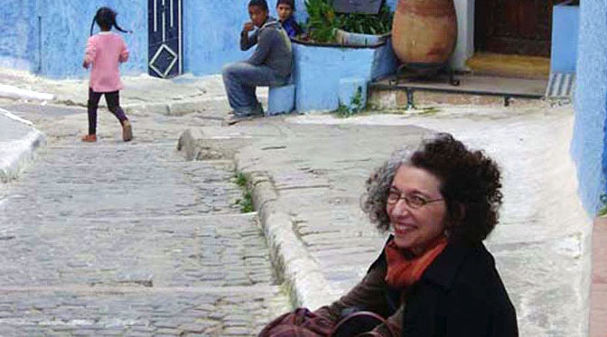 Woman sitting on a curb with children playing nearby in Rabat, Morocco