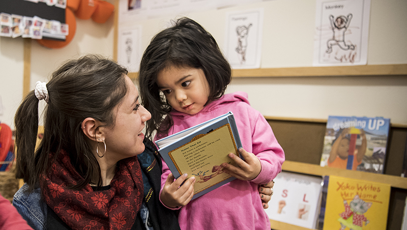 Child looks at teacher while holding book