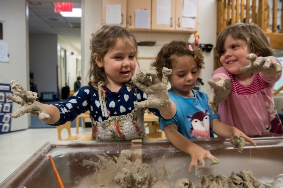 Three children play with clay at the clay table