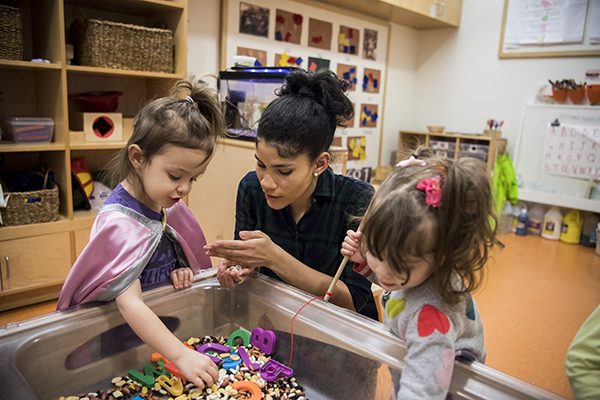 Teacher and children exploring sensory table