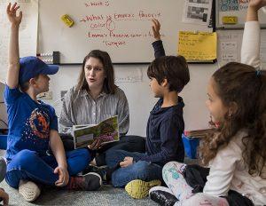 Teacher reading to three students
