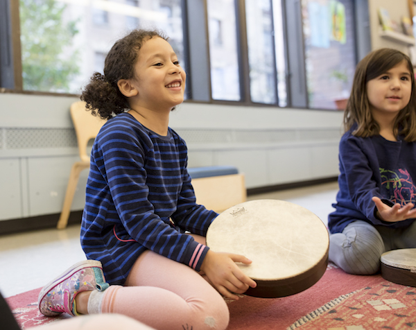 Smiling child with hand drum