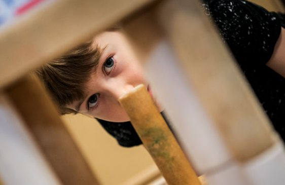 boy looking through a block city he built with wooden blocks