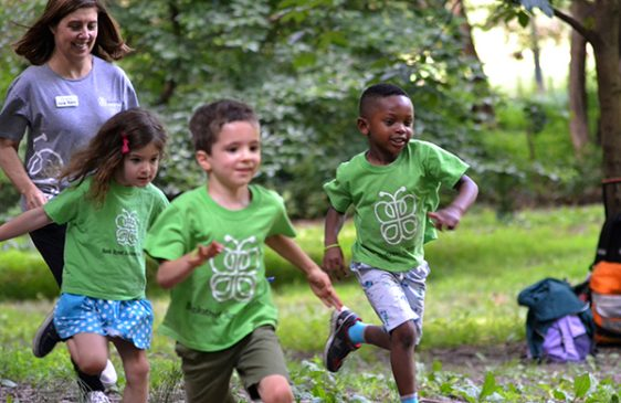 Campers run on the grass wearing their lime green camp shirts