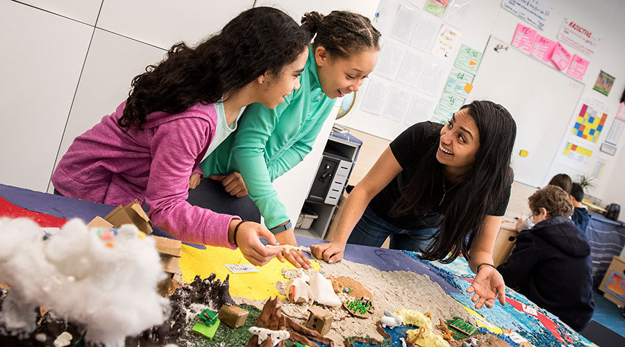 A grad students works with middle school students on a social studies project
