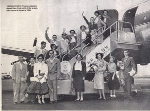 In this black and white photo dozens of people, wearing suits board a plane.
