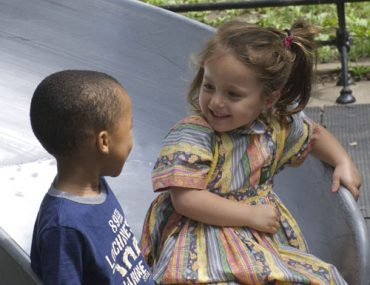2 chidren smiling at one another and playing