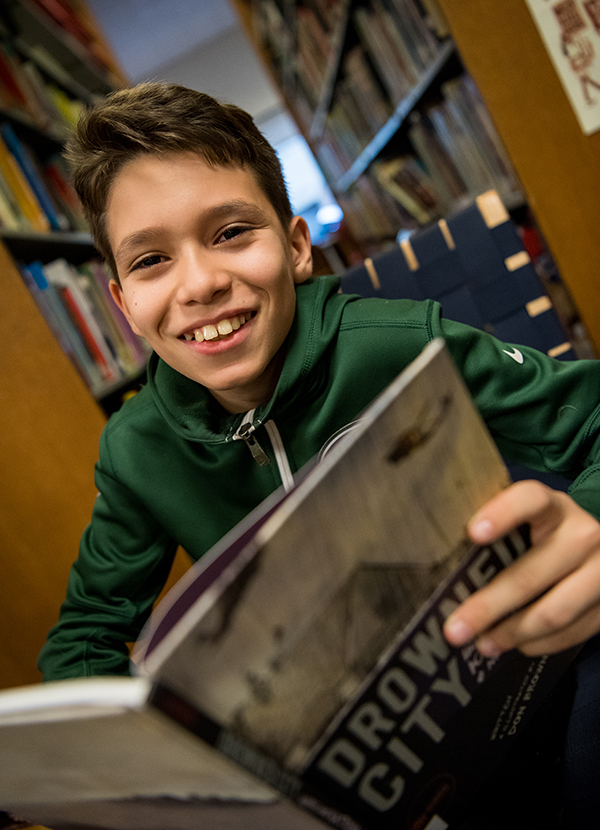 13/14s student smiling while holding book