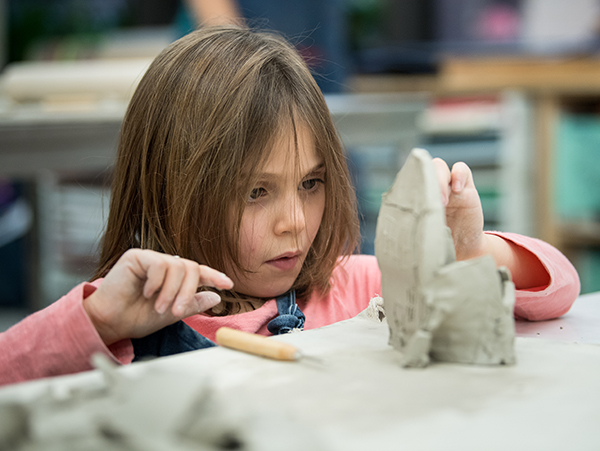 Child molding clay sculpture