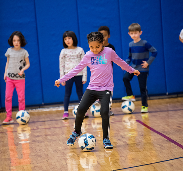 Children play soccer in the gym